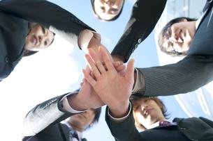 円陣を組むビジネスマンとビジネスウーマンの写真素材 [FYI04544835]