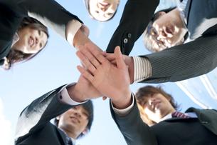 円陣を組むビジネスマンとビジネスウーマンの写真素材 [FYI04544837]