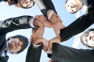 スクラムを組むビジネスマンとビジネスウーマンの写真素材 [FYI04544838]