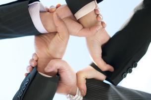 スクラムを組むビジネスマンとビジネスウーマンの手元の写真素材 [FYI04544839]