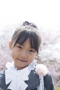 桜の前で微笑む小学生の写真素材 [FYI04545024]