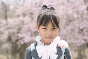 桜の前で微笑む小学生の写真素材 [FYI04545033]