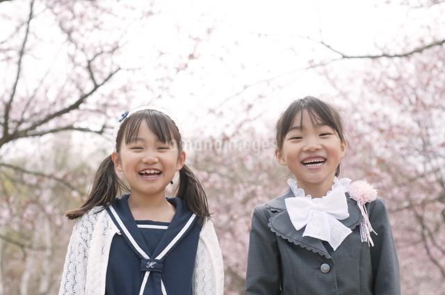 桜の前で微笑む小学生の写真素材 [FYI04545064]