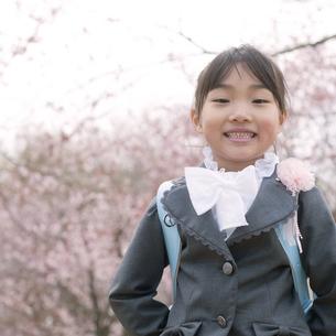 桜の前で微笑む小学生の写真素材 [FYI04545067]