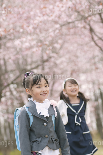 桜の前で微笑む小学生の写真素材 [FYI04545072]