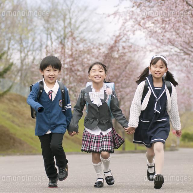 桜並木道を歩く小学生の写真素材 [FYI04545078]