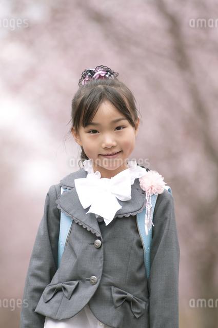 桜の前で微笑む小学生の写真素材 [FYI04545090]