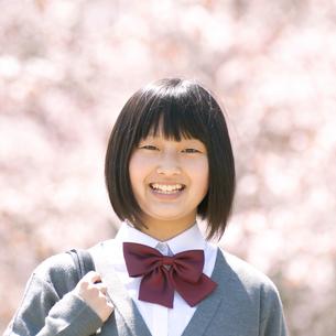 桜の前で微笑む中学生の写真素材 [FYI04545299]
