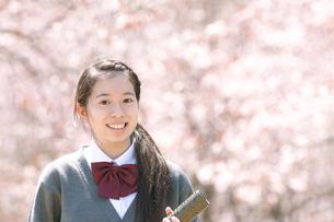 桜の前で微笑む中学生の写真素材 [FYI04545303]