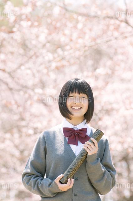 桜の前で微笑む中学生の写真素材 [FYI04545323]