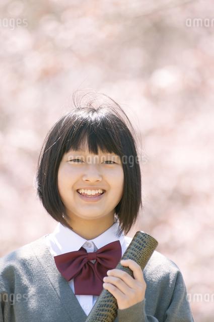桜の前で微笑む中学生の写真素材 [FYI04545328]