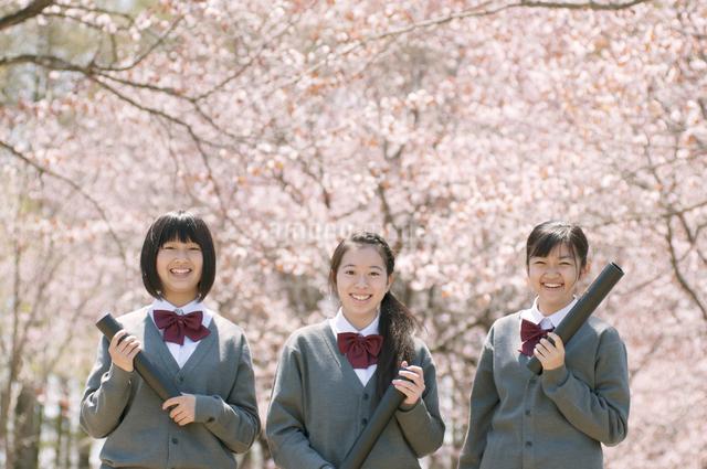 桜の前で微笑む中学生の写真素材 [FYI04545333]