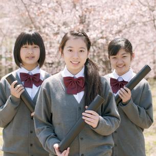 桜の前で微笑む中学生の写真素材 [FYI04545336]