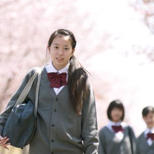 桜の前で微笑む中学生の写真素材 [FYI04545350]