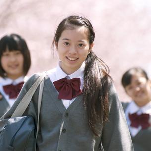 桜の前で微笑む中学生の写真素材 [FYI04545355]