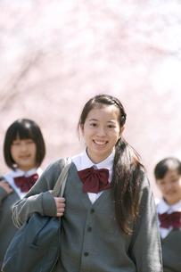 桜の前で微笑む中学生の写真素材 [FYI04545358]