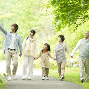 新緑の中で手をつなぐ3世代家族の写真素材 [FYI04545383]