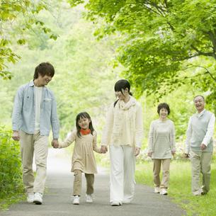 新緑の中で手をつなぐ3世代家族の写真素材 [FYI04545391]