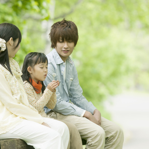 ベンチに座り微笑む家族の写真素材 [FYI04545399]