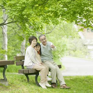 ベンチに座り微笑む祖父母と孫の写真素材 [FYI04545400]
