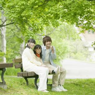 ベンチに座り微笑む家族の写真素材 [FYI04545402]