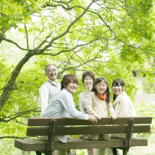 ベンチに座り微笑む3世代家族の写真素材 [FYI04545408]