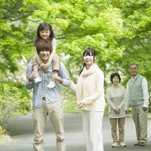 新緑の中を歩く3世代家族の写真素材 [FYI04545413]