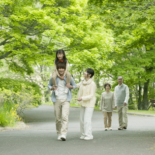 新緑の中を歩く3世代家族の写真素材 [FYI04545417]