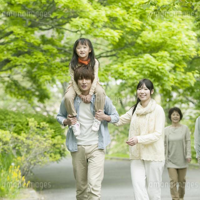 新緑の中を歩く3世代家族の写真素材 [FYI04545419]