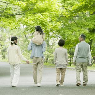 新緑の中を歩く3世代家族の後姿の写真素材 [FYI04545423]