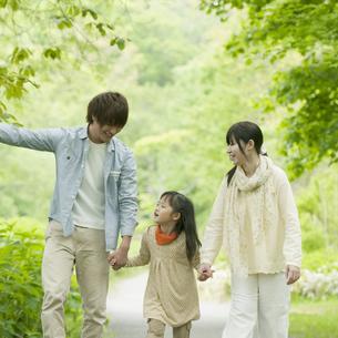 新緑の中で手をつなぐ家族の写真素材 [FYI04545432]