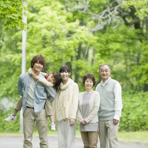 新緑の中で微笑む3世代家族の写真素材 [FYI04545447]