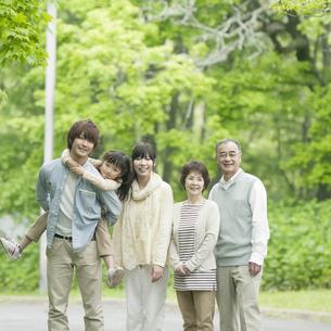 新緑の中で微笑む3世代家族の写真素材 [FYI04545448]