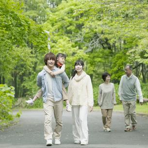 新緑の中を歩く3世代家族の写真素材 [FYI04545449]
