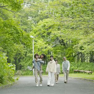 新緑の中を歩く3世代家族の写真素材 [FYI04545450]