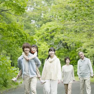 新緑の中を歩く3世代家族の写真素材 [FYI04545451]