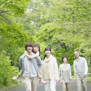 新緑の中を歩く3世代家族の写真素材 [FYI04545452]