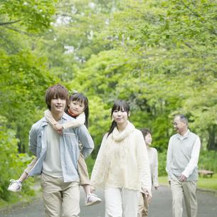 新緑の中を歩く3世代家族の写真素材 [FYI04545455]