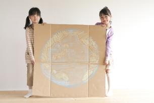 地球の絵を描いた段ボールを持ち微笑む子供たちのイラスト素材 [FYI04545461]