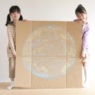 地球の絵を描いた段ボールを持ち微笑む子供たちのイラスト素材 [FYI04545463]