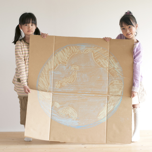 地球の絵を描いた段ボールを持ち微笑む子供たちのイラスト素材 [FYI04545464]