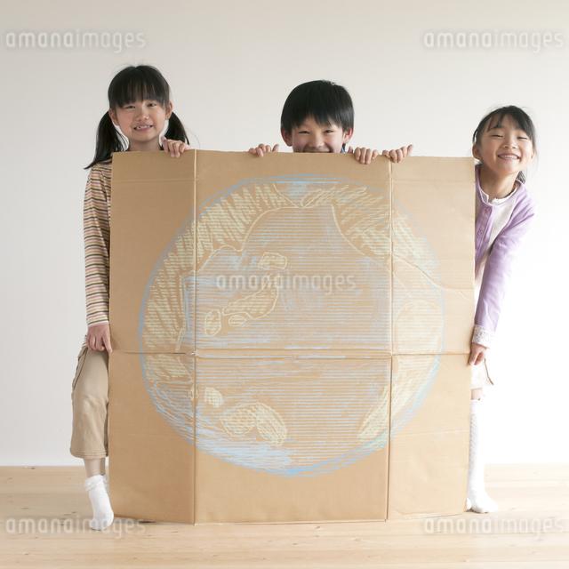 地球の絵を描いた段ボールを持ち微笑む子供たちのイラスト素材 [FYI04545469]