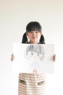自分の描いた絵を見せる女の子のイラスト素材 [FYI04545477]