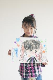 自分の描いた絵を見せる女の子の写真素材 [FYI04545481]
