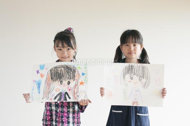 自分の描いた絵を見せる2人の女の子のイラスト素材 [FYI04545483]