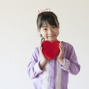 ハートを持ち微笑む女の子の写真素材 [FYI04545505]