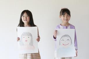 自分の描いた絵を見せる2人の女の子のイラスト素材 [FYI04545523]