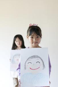 自分の描いた絵を見せる2人の女の子のイラスト素材 [FYI04545528]