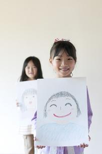 自分の描いた絵を見せる2人の女の子のイラスト素材 [FYI04545529]