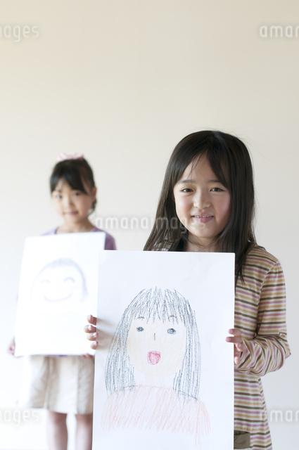 自分の描いた絵を見せる2人の女の子のイラスト素材 [FYI04545532]